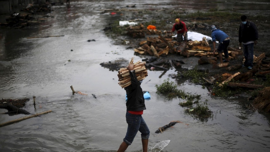 A man carries wood for pyre to burn the bodies of victims of Saturday's earthquake, during the cremation along a river in Kathmandu, Nepal April 28, 2015. REUTERS/Adnan Abidi - RTX1AOND