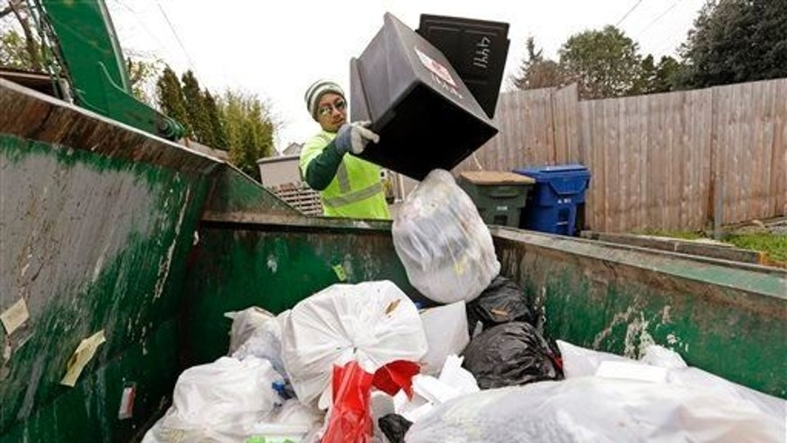 In this unrelated photo taken Monday, Dec. 22, 2014, a garbage collector empties a small residential garbage bin into his truck as larger yard waste and recycling bins stand behind, in Seattle.