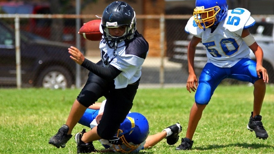 Young american football player running back breaking away from an attempted tackle.