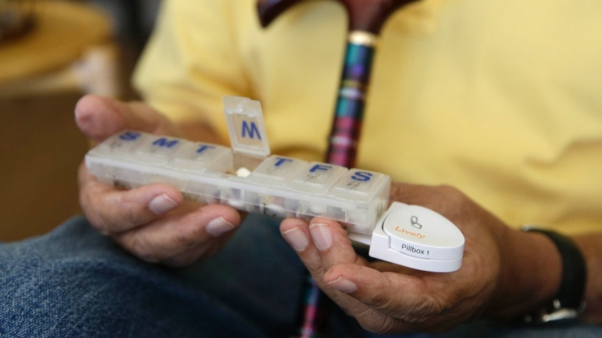 In this March 17, 2015 photo, 81-year-old Bill Dworsky holds his pill container with a motion sensor attached at his home in San Francisco. (AP Photo/Eric Risberg)