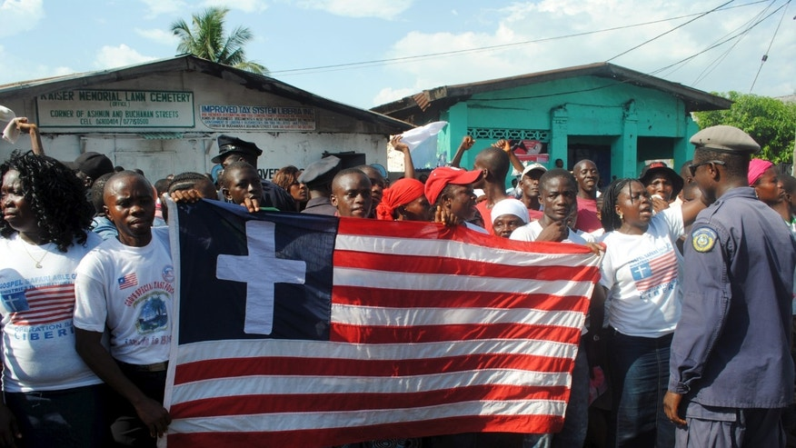 People hold the Liberian flag with a Christian cross on it during an official celebration of the country being declared Ebola-free, in Monrovia, Liberia, May 11, 2015. REUTERS/James Giahyue - RTX1CHUC