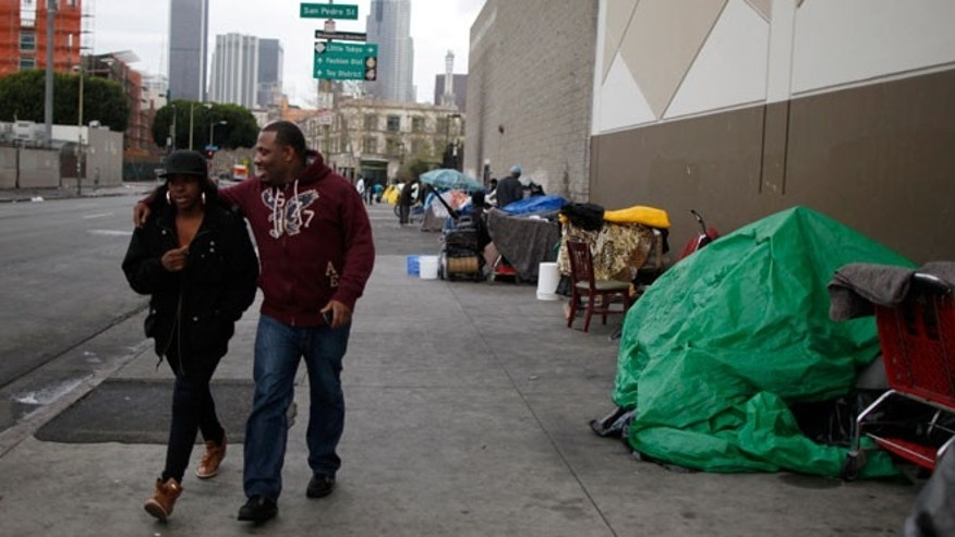 A couple walks past tents on downtown Los Angeles' Skid Row, March 7, 2013. Los Angeles has asked the U.S. Supreme Court to allow police and city workers to seize or destroy property that homeless people leave unattended on sidewalks, saying Skid Row homeless encampments presented a public-health risk. According to the Los Angeles County Department of Public Health, some 11 people have died from tuberculosis since 2007, and of the 78 people infected, 60 were homeless.
