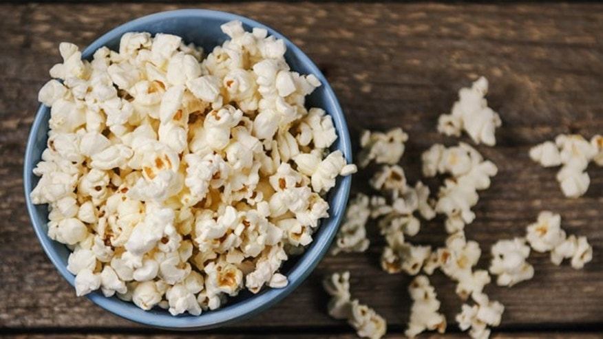 Popcorn in a bowl on wooden table