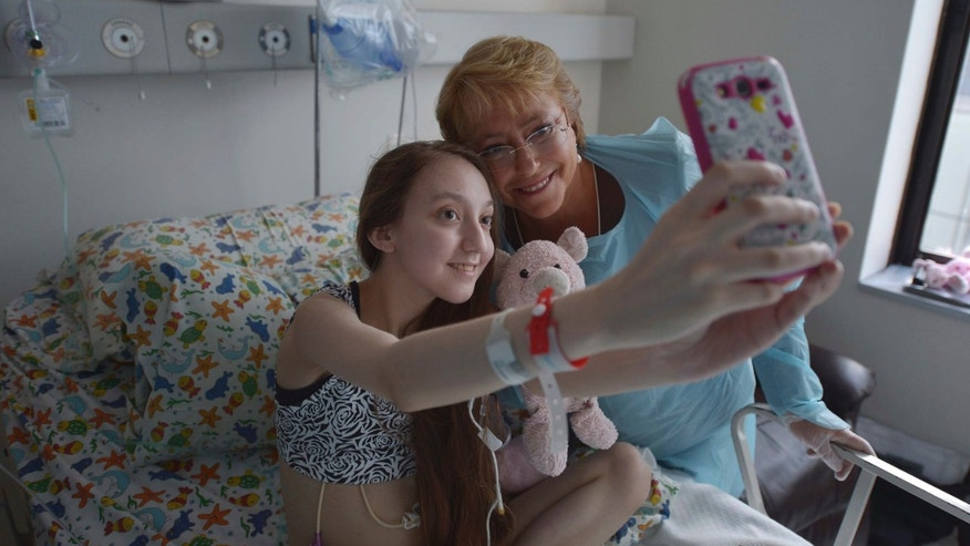 FILE - In this Feb 28, 2015 file photo released by Chile's Presidential Press Office, Valentina Maureira takes a photo of herself with President Michelle Bachelet, at the Catholic University hospital in Santiago, Chile. The girl, ailing from cystic fibrosis, who made a public plea for permission to end her life has died. Her father, Fredy Maureira, confirmed that Valentina passed away on Thursday, May 13, 2015, to local Radio Bio Bio, saying the 14-year-old is finally resting in peace. (AP Photo/Chile Presidential Press Office, Ximena Navarro, File)