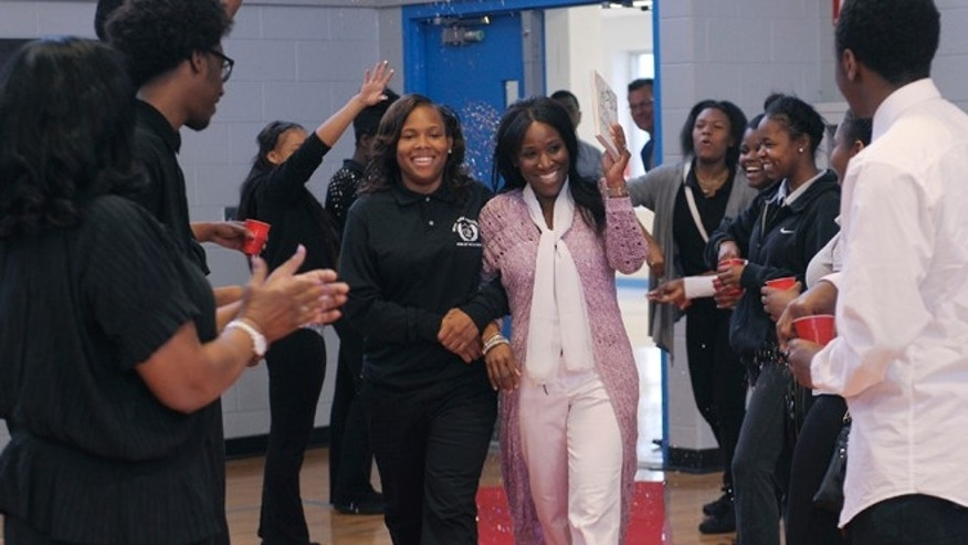 May 19, 2015: West Side Academy senior A'Ja Booth, left, and her teacher Nadirah Muhammad enter a welcome rally for Booth at the school in Detroit.