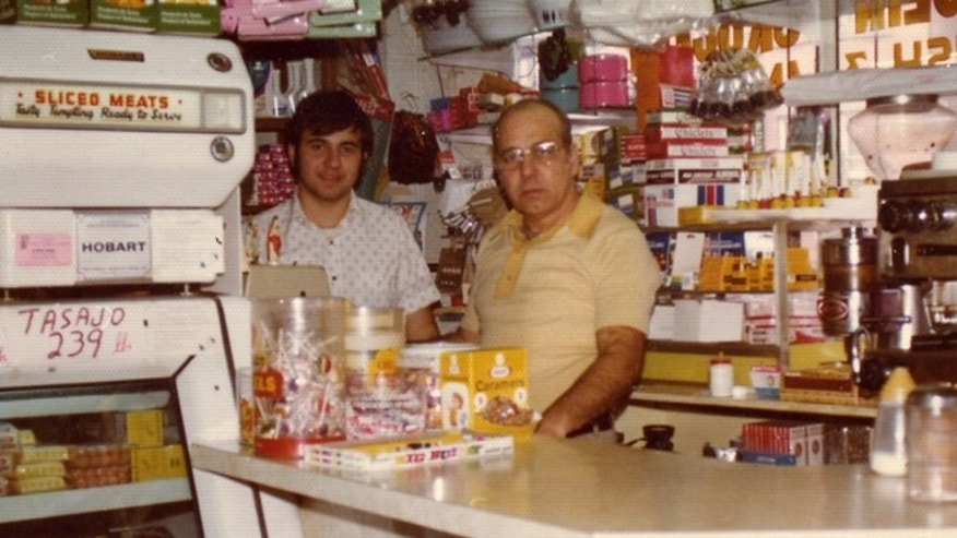 In this undated photo, a teenage Dr. Manny (left) and his father (right) pose in the family store in West New York, NJ.