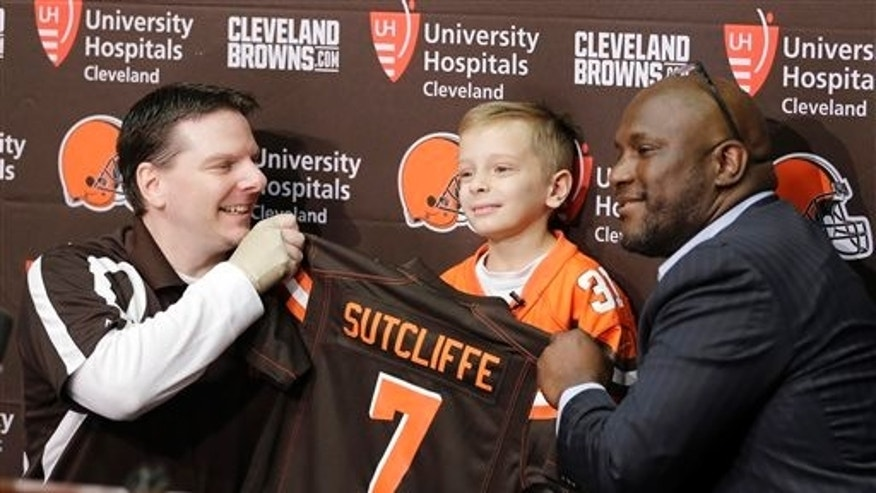 Derek Sutcliffe, left, and Cleveland Browns general manager Ray Farmer, right, hold up a jersey for Dylan Sutcliffe, 9, during an NFL football news conference, Tuesday, June 2, 2015, in Berea, Ohio. (AP Photo/Tony Dejak)