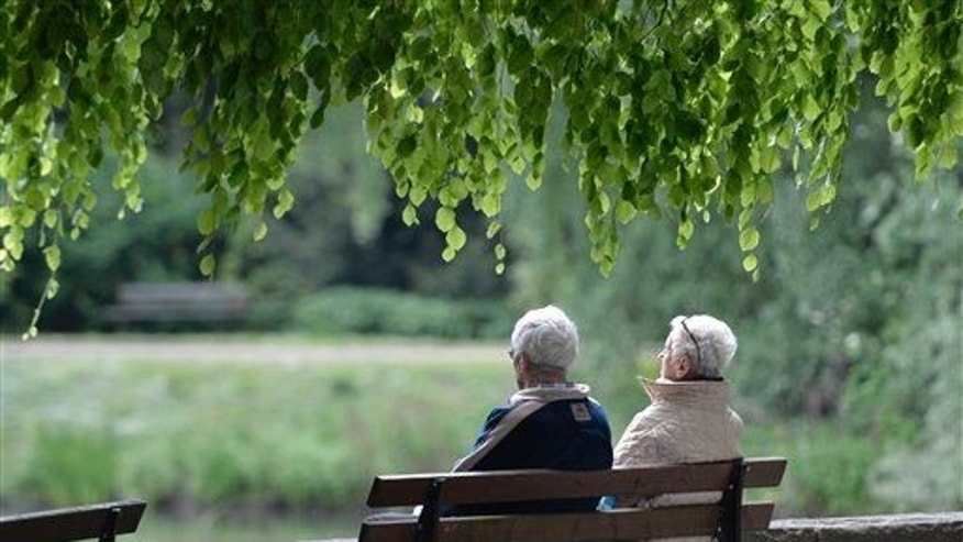 In this May 14, 2014 file photo an elderly couple sits on a bench in a park in Gelsenkirchen, Germany.