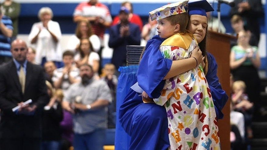 In this May 31, 2015 photo, Tri-City High School Valedictorian Bethany Daniels hugs Jordan Planitz after he received an honorary diploma during the school's commencement ceremony in Buffalo, Ill. The six year-old Planitz suffers from a terminal condition characterized by brain abnormalities and excess fluid inside the skull.