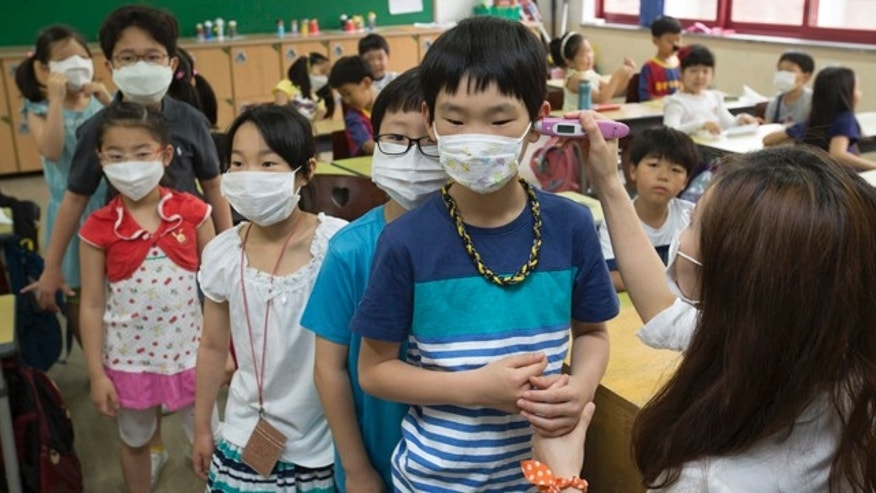 June 8, 2015: A teacher, right, checks temperature of a student as they wear masks as a precaution against Middle East Respiratory Syndrome virus at Midlong Elementary School in Seoul, South Korea. South Korea on Monday reported its sixth death from MERS as authorities were bolstering measures to stem the spread of the virus that has left dozens of people infected. (Yun Dong-jin/Yonhap via AP)