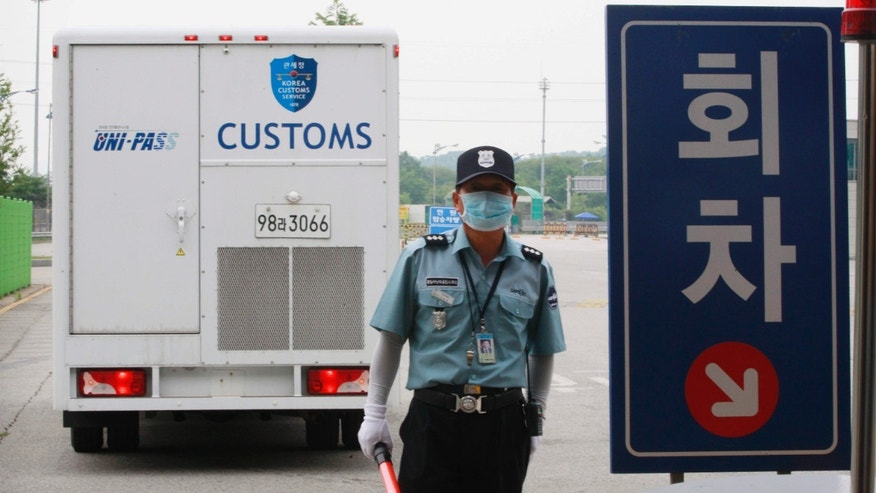 June 13, 2015: A South Korean security person wears a mask as a precaution against the Middle East Respiratory Syndrome (MERS) virus at the customs, immigration and quarantine gate in Paju, South Korea, near the border village of Panmunjom, South Korea.