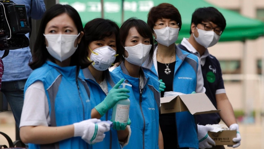 June 13, 2015: South Korean health workers from a community health center wearing masks as a precaution against MERS, Middle East Respiratory Syndrome, virus, wait to check examinees' temperature and to sanitzie their hands at a test site for a civil service examination in Seoul, South Korea.