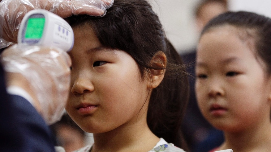 June 17, 2015: An unidentified student is checked her temperature as a precaution against MERS (Middle East Respiratory Syndrome) at Gwanghui Elementary School in Seoul, South Korea