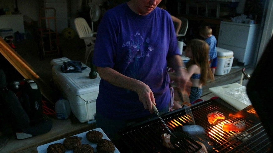 SEBASTIAN, FL - SEPTEMBER 28:  Jennifer Carr uses a grill outside to cook some chicken and burgers since their house is without electricity after Hurricane Jeanne knocked out the power September 28, 2004 in Sebastian, Florida. Many people throughout the region are still without power.  (Photo by Joe Raedle/Getty Images)