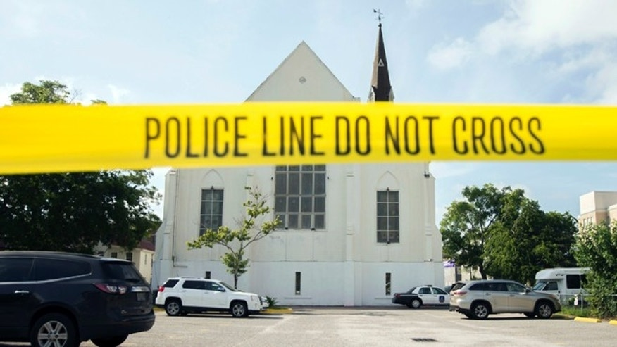 June 19, 2015: Police tape surrounds the parking lot behind the AME Emanuel Church as FBI forensic experts work the crime scene in Charleston, S.C.