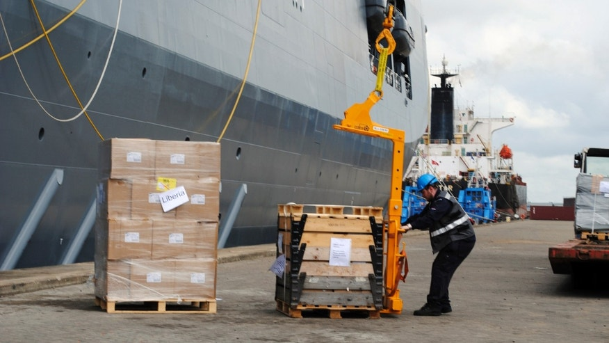 A workers unloads emergency health supplies provided by the Netherlands to aid in the fight against the Ebola virus at the port of Liberia in Monrovia November 24, 2014. REUTERS/James Giahyue