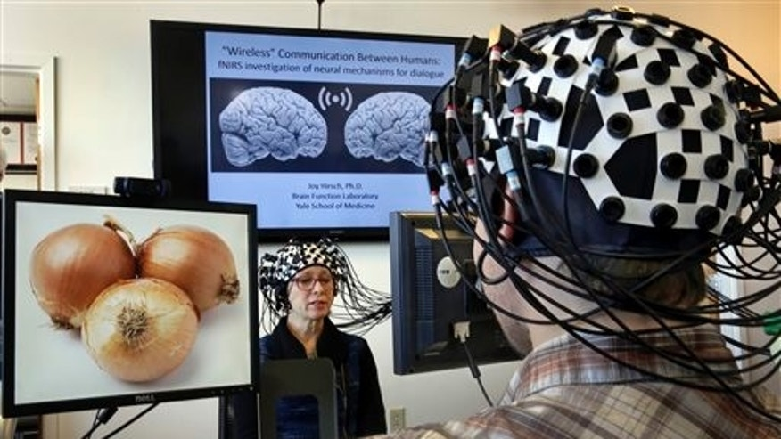 Shaw Bronner, left, and Shaul Yahil, two researchers at the Yale Brain Function Lab, describe images on their computer screens to each other while their brain activity is mapped during a demonstration of the technology in New Haven, Conn. on Friday, March 13, 2015. (AP Photo/Richard Drew)