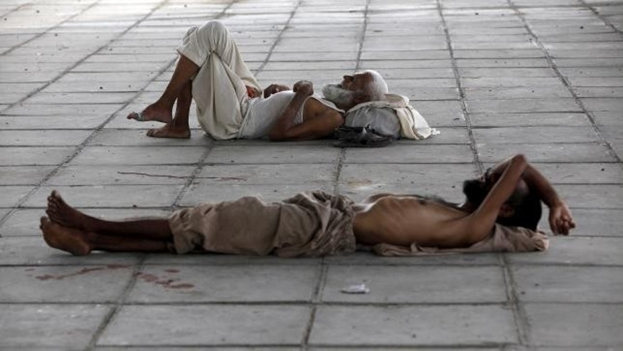 June 22, 2015: Men sleep in shade under a bridge during intense hot weather in Karachi, Pakistan.
