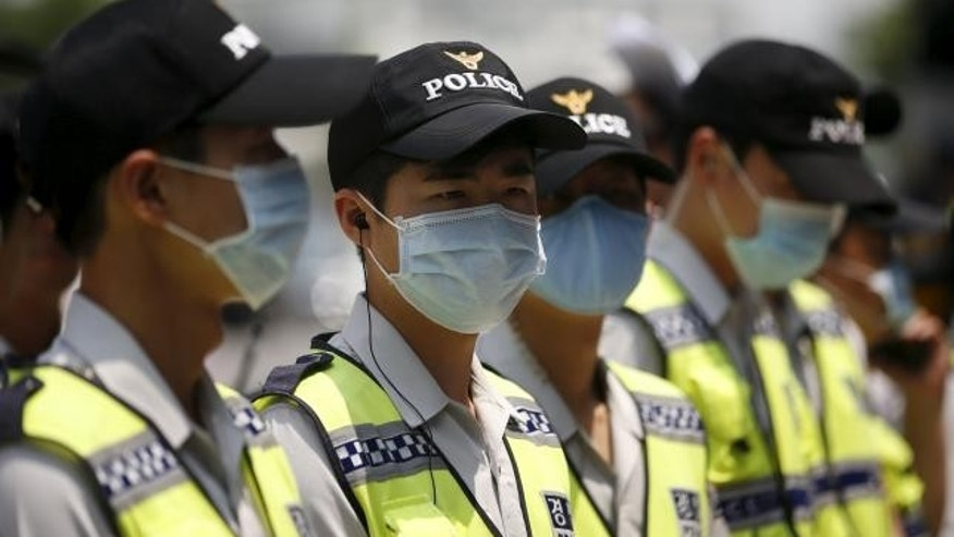 June 22, 2015: Policemen wearing masks to prevent contracting Middle East Respiratory Syndrome (MERS) stand guard in front of Japanese Embassy in Seoul, South Korea.