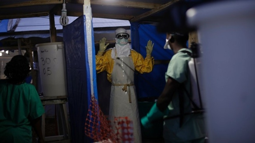FILE - In this Thursday Nov. 20, 2014 file photo, an MSF Ebola heath worker is sprayed as he leaves the contaminated zone at the Ebola treatment centre in Gueckedou, Guinea. (AP Photo/Jerome Delay, File)