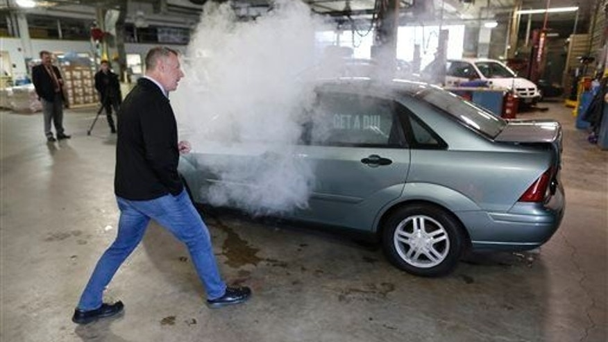 In this April 2015 photo, reporter Trevor Hughes gets a closer look as smoke billows out of car used in a campaign by the Colorado Department of Transportation to fight stoned driving.