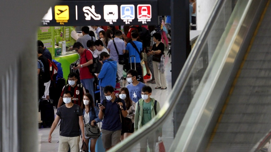 A group of tourists wear masks to prevent contracting Middle East Respiratory Syndrome (MERS) as they arrive at Bangkok's Suvarnabhumi International Airport, Thailand, June 21, 2015. REUTERS/Kerek Wongsa - RTX1HFPK