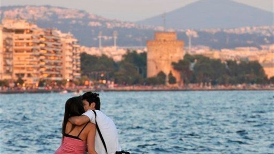 A couple kiss each other at the seaside of Thessaloniki, Greece.