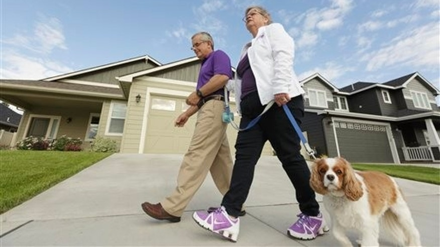 Amy Shives, right, and her husband George walk their cavalier King Charles spaniel Chester in their neighborhood, Wednesday, June 3, 2015, in Spokane, Wash. Amy Shives was diagnosed with early onset Alzheimer's disease in 2011 and has since been involved with the Alzheimer's  Association. (AP Photo/Young Kwak)