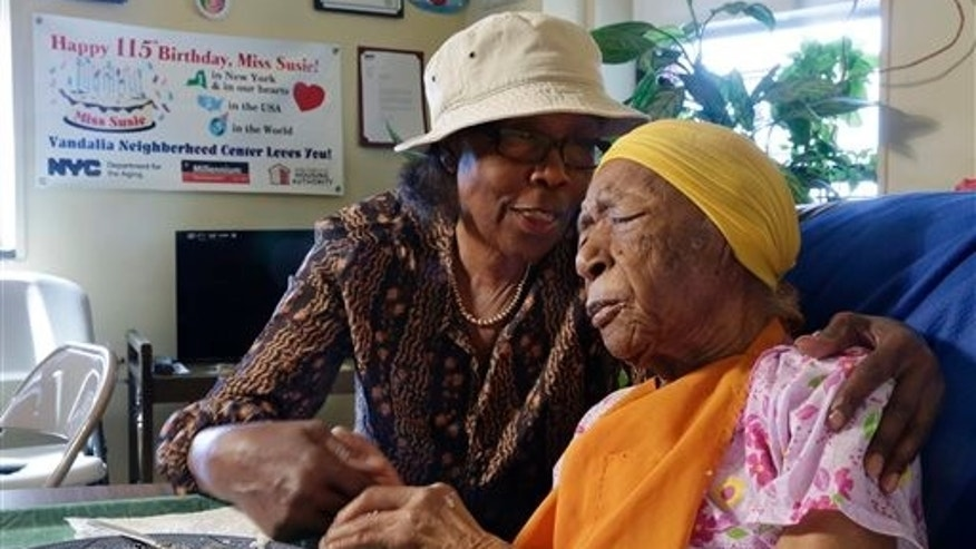 In this Monday, June 22, 2015 photo, Susannah Mushatt Jones, 115, right, is embraced by her niece Lois Judge in her room at the Vandalia Avenue Houses, in the Brooklyn borough of New York. Jones and Emma Morano, of Verbania, Italy, who is also 115, are believed to be the last two people in the world with birthdates in the 1800s. (AP Photo/Richard Drew)