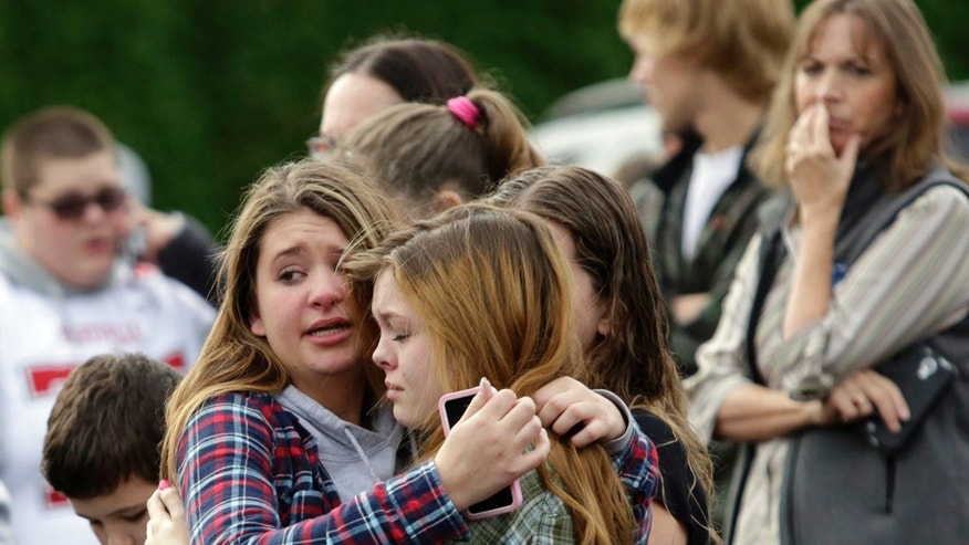 Two girls hug at Shoultes Gospel Hall church where families are reuniting after an active shooter situation at Marysville-Pilchuck High School in Marysville, Washington October 24, 2014.  REUTERS/Jason Redmond