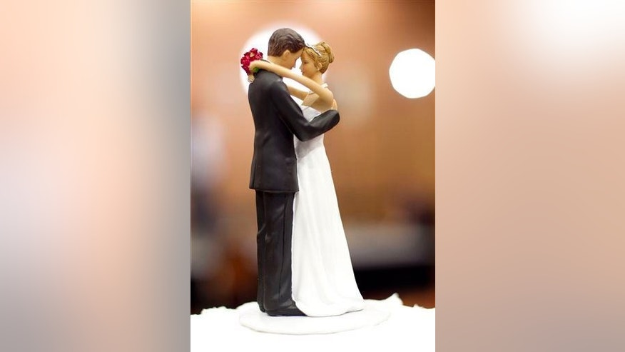 Figurines of a bride and a groom sit atop a wedding cake in Raleigh, N.C., on Tuesday May 8, 2012.