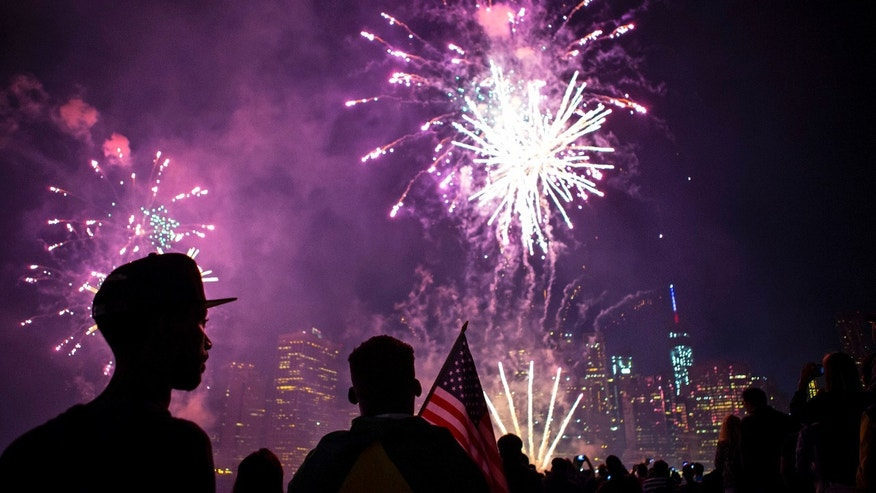 The skyline of lower Manhattan is seen as spectators watch Macy's Fourth of July fireworks explode over the East River in New York July 4, 2014. REUTERS/Eric Thayer