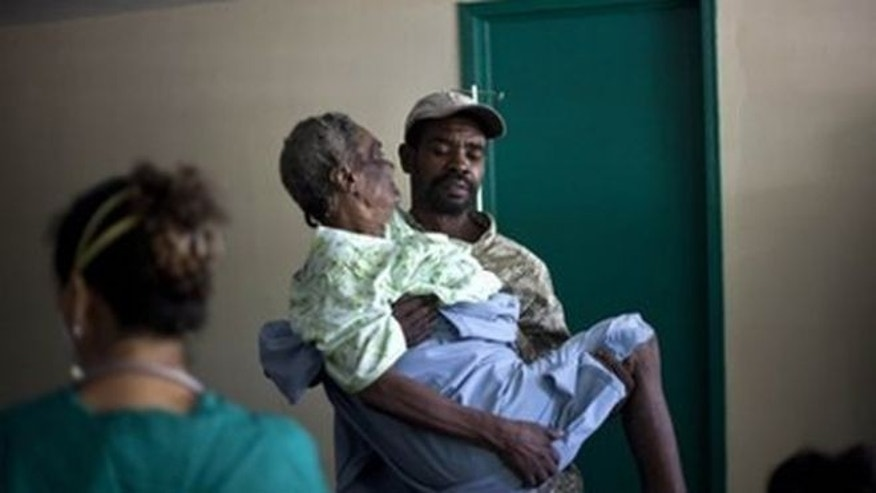 In this photo from Nov. 8, 2010, a woman suffering from cholera symptoms is carried by a volunteer at the hospital in Archaie, Haiti. (AP Photo)