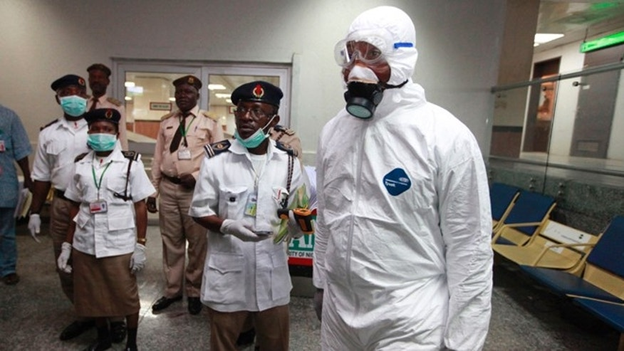 Nigerian health officials wait to screen passengers at the arrival hall of Murtala Muhammed International Airport in Lagos, Nigeria, Monday, Aug. 4, 2014. Nigerian authorities on Monday confirmed a second case of Ebola in Africa's most populous country, an alarming setback as officials across the region battle to stop the spread of a disease that has killed more than 700 people. (AP Photo/Sunday Alamba)