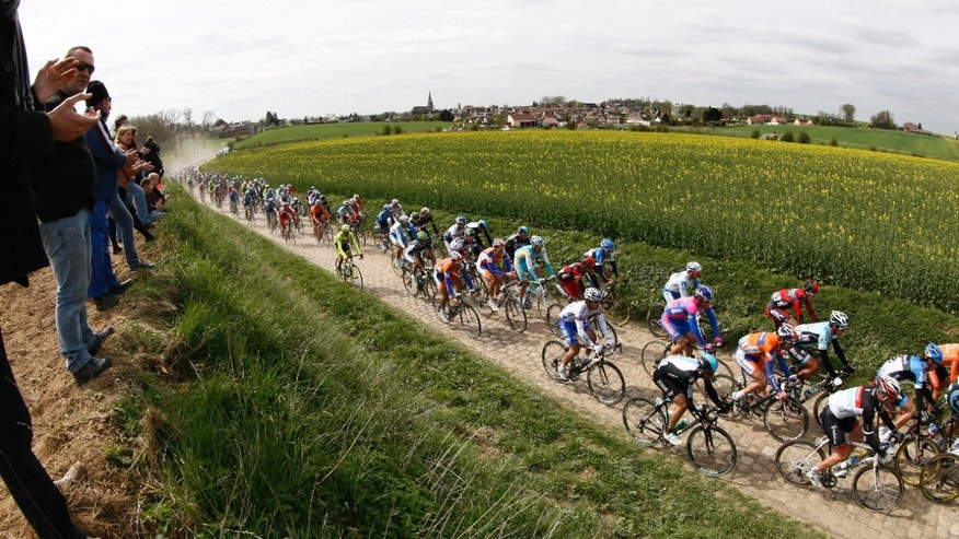 Riders cycle on a cobblestone-paved section of road during the classic cycling race Paris-Roubaix in Troisvilles , northern France, Sunday April 8, 2012. (AP Photo/Michel Spingler).