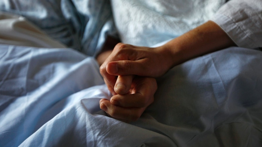 A woman holds the hand of her mother who is dying from cancer during her final hours at a palliative care hospital.
