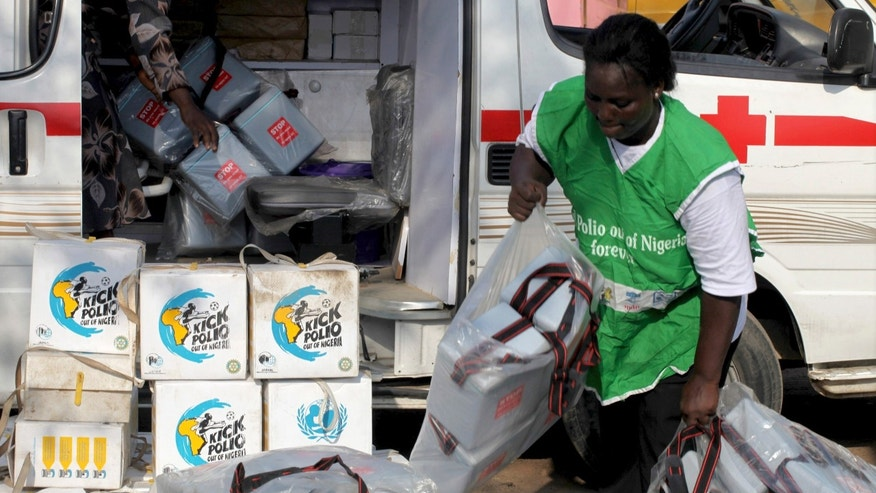 A local health worker carries vaccination kits into a vehicle at a distribution centre ahead of the start of a nationwide polio immunization campaign on Wednesday, in Lagos February 21, 2011.   REUTERS/Akintunde Akinleye