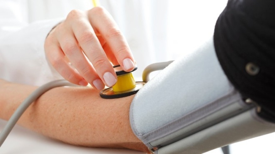 Close-up of Doctor/nurse checking blood pressure with stethoscope