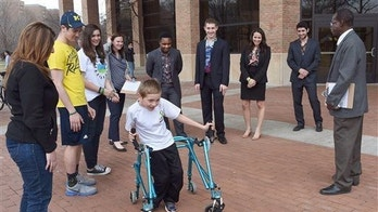 In a photo taken April 16, 2015,  Braden Gandee, 8, who has cerebral palsy, tries out his new customized walker at the Design Expo in Ann Arbor, Mich.