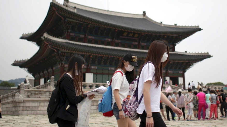 June 7, 2015: Tourists wear masks as a precaution against MERS, Middle East Respiratory Syndrome, virus as they visit Gyeongbok Palace, one of South Korea's well-known landmarks, in Seoul, South Korea.