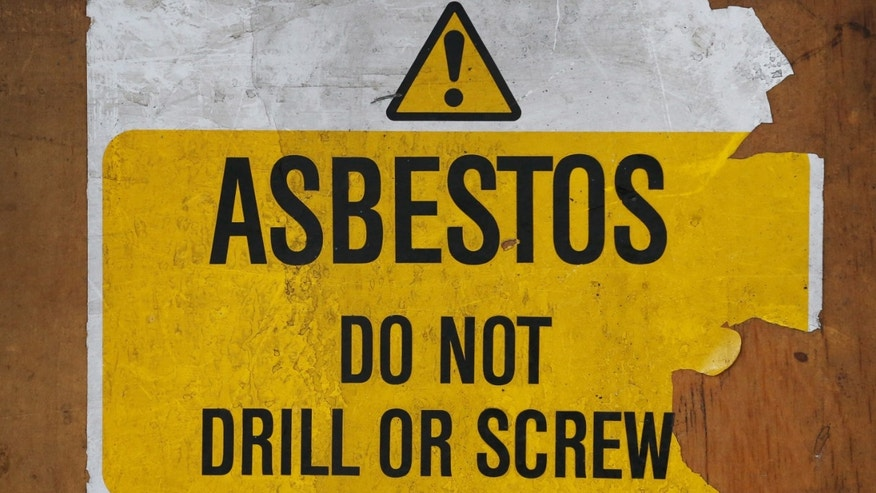 LONDON, ENGLAND - OCTOBER 11:  A sign warns of asbestos danger at a former Royal Mail sorting office on October 11, 2013 in London, England.  (Photo by Peter Macdiarmid/Getty Images)