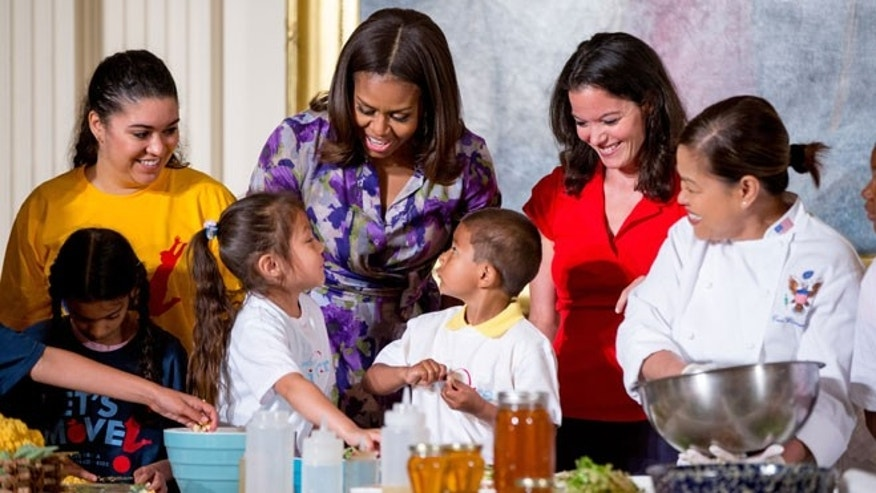 "First lady Michelle Obama, accompanied by Lets Move! Executive Director Deb Eschmeyer, second from right, talks with Oneida Gonzalez, 5, center left, and Jefferson Lopez-Martinez, 5, center right, of CentroNia Daycare Center in Washington, D.C. as they help prepare food harvested from the White House Kitchen Garden along with fellow children from all over the country who participated in events with the ""Let's Move!"" campaign, Wednesday, June 3, 2015, in the East Room at the White House in Washington. Eschmeyer grew up on an Ohio dairy farm as the youngest of seven siblings. She faces two particular challenges in the final months of the Obama administration. One is keeping intact a federal law that made school foods healthier. The other is helping the first lady Michelle Obama's initiative continue after Mrs. Obama leaves the White House."