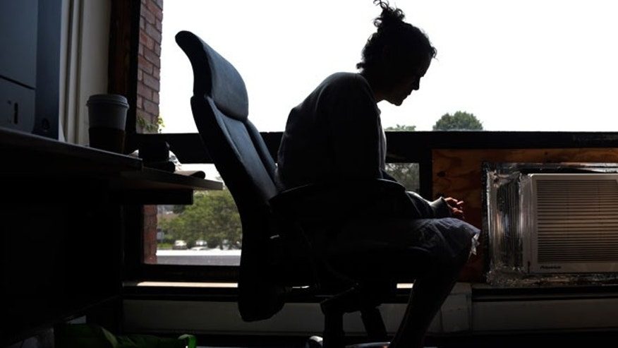 In this July 10, 2015, photo, a woman speaks to The Associated Press inside the police station in Gloucester, Mass. The woman voluntarily came to the police for help kicking her heroin addiction. Gloucester is taking a novel approach to the war on drugs, making the police station a first stop for addicts on the road to recovery. Addicts can turn in their drugs to police, no questions asked, and officers, volunteers and trained clinicians help connect them with detox and treatment services.