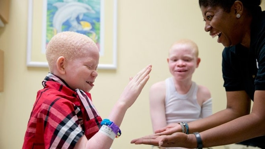 Monica Watson, right, with the Global Medical Relief Fund, plays with Mwigulu Magesa, 12, left, and Emmanuel Rutema, 13, during a fitting for prosthetic limbs at the Shriners Hospital for Children in Philadelphia on Thursday, July 23, 2015. Witch doctors often lead brutal attacks in Tanzania to use albino body parts in potions they claim bring riches.