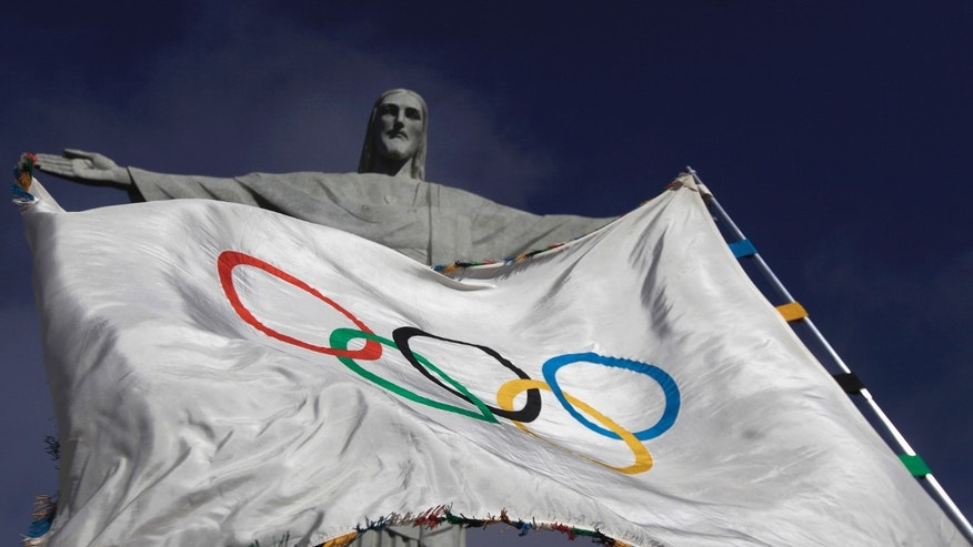 "Aug. 19, 2012: The Olympic Flag flies in front of ""Christ the Redeemer"" statue during a blessing ceremony in Rio de Janeiro."