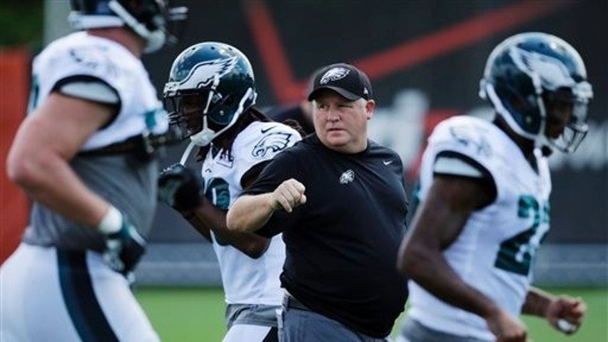 Philadelphia Eagles head coach Chip Kelly watches his team warm up before practice at NFL football training camp, Wednesday, Aug. 12, 2015, in Philadelphia. (AP Photo/Matt Slocum)