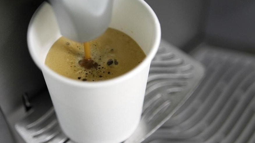 A coffee machine pours coffee into a paper cup in Kiev March 1, 2012.   REUTERS/Gleb Garanich