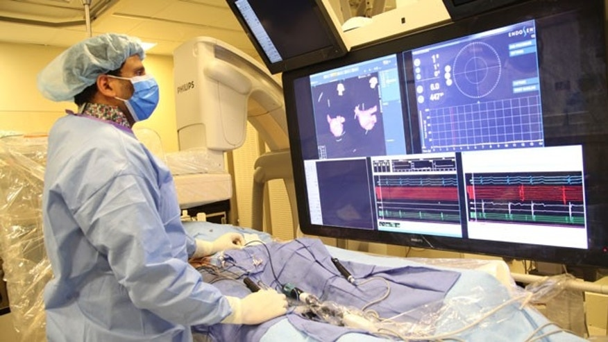In this undated image provided on Saturday Aug. 29, 2015 by Mount Sinai Hospital in New York shows Dr Vivek Reddy as he checks the screen while doing a surgery to implant the new tiny wireless pacemaker at the Mount Sinai hospital in New York . Unlike traditional pacemakers — which need a generator and wires and are implanted via surgery — the new pacemaker is a wireless tiny tube that can be attached to the right side of the heart using a catheter inserted through the leg.