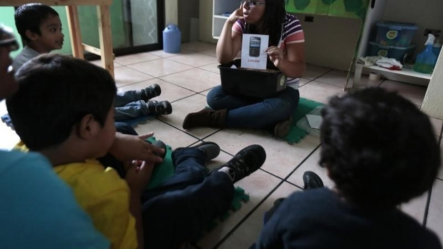 A teacher talks to children during class at the therapy and development centre for autistic kids in the Asociacion Guatemalteca por el Autismo, or Guatemalan Association for Autism, building in Guatemala City March 13, 2014. (REUTERS/JORGE DAN LOPEZ)