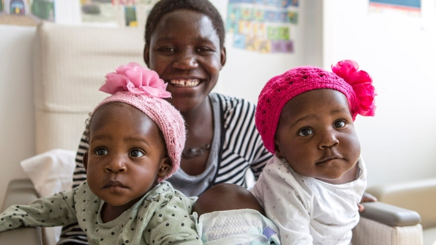 Acen (left) and Apio (right) Akello arrived at Nationwide Children`s Hospital conjoined as one and were separated during a 16-hour surgery on Sept. 3, 2015. The girls are pictured here in their hospital room with their mother, Ester Akello. (image courtesy Nationwide Children's Hospital)